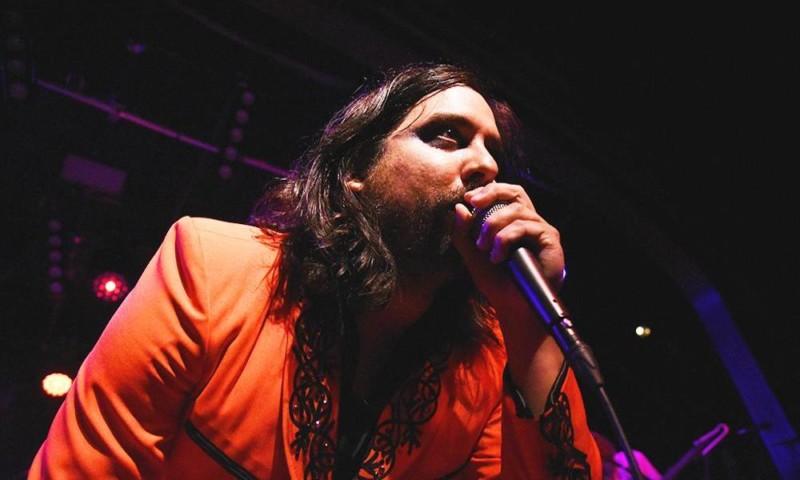 Honus Honus singing onstage in an orange blazer.