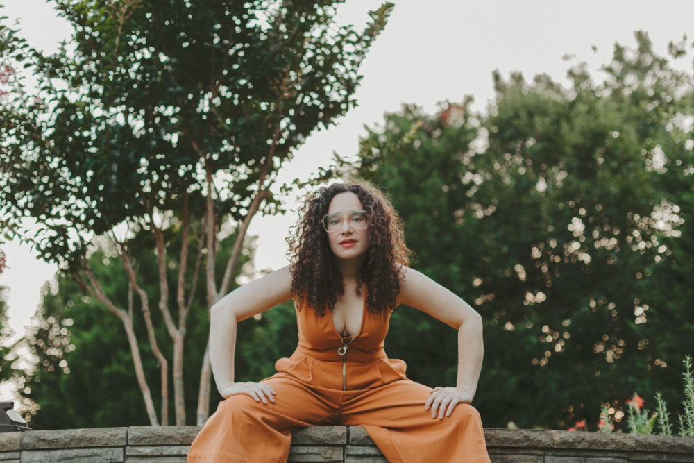 Musician Rachel Kiel crouches in a powerful stance, surrounded by trees and wearing an orange pantsuit