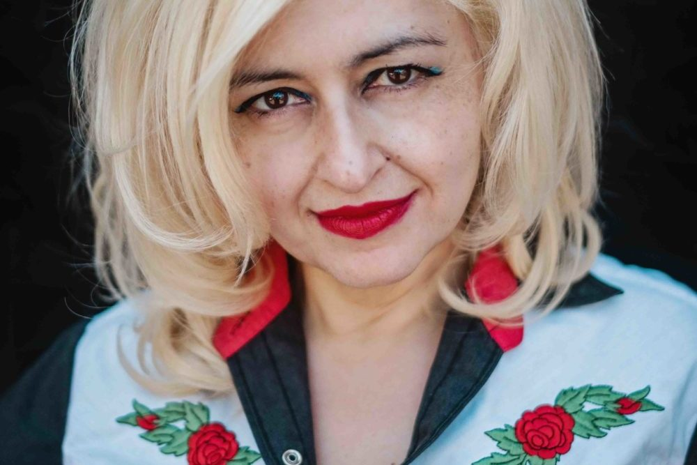 Melbourne-based concert promoter Mary Mihelakos wears a cowboy shirt with embroidered red roses that match her bright lipstick and blonde bouffant