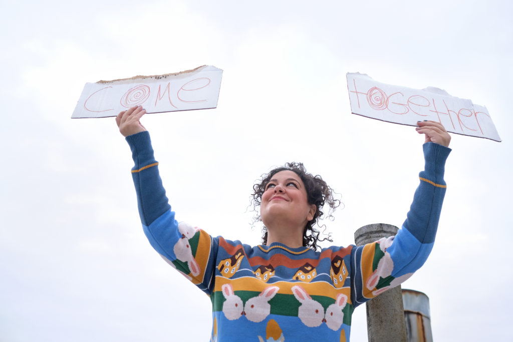 "musician Tamar Haviv holds up cardboard signs that say ""Come Together"""