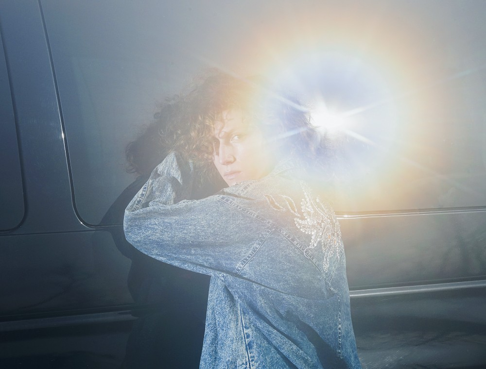musician Squirrel Flower, wearing a denim jacket, stands partially turned away from the camera, with bright glare from the sun partially obscuring the image